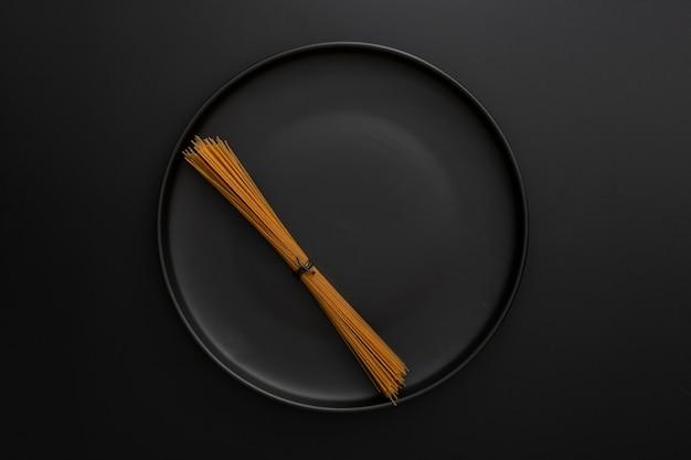 Donkere achtergrond met donkere plaat met pasta