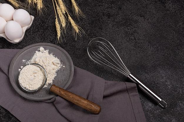 Donkere achtergrond voor het bakken met eieren, meel, tarwe, garde