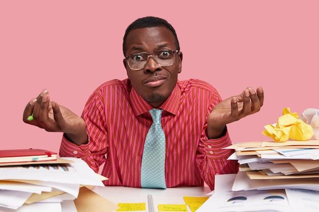 Donkere administratieve manager spreidt handpalmen met aarzeling, controleert rekeningen in documentatie, heeft een twijfelachtige blik