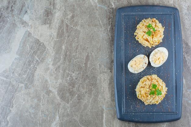 Donkere bord van gekookte eieren en macaroni op marmeren oppervlak.
