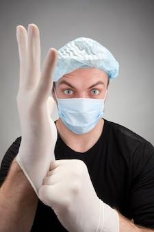 Donkere chirurg die handschoenen draagt
