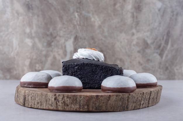 Donkere chocolade brownies cake en mini mousse gebak aan boord op het marmer.