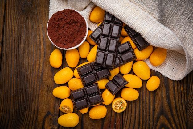 Donkere chocolade en kumquat op een houten tafel