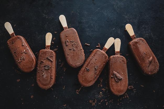 Donkere chocolade ijs ijslollys met geraspte chocolade op donkere plaat. bovenaanzicht.