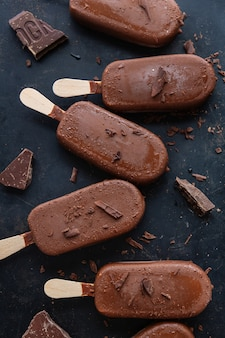Donkere chocolade ijs ijslollys met geraspte chocolade op donkere plaat. detailopname