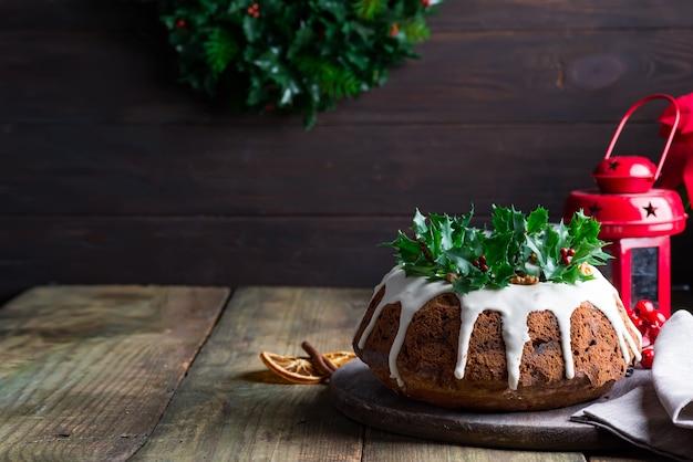 Donkere chocoladecake van kerstmis verfraaid met witte suikerglazuur en hulstbessentakken met rode lantaarn donkere houten