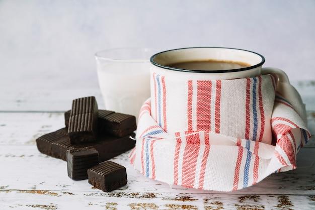 Donkere chocoladereep; melk en koffie mok omwikkeld met servet op houten tafel