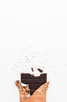 Donkere chocoladereep verpakt in gouden foliedocument op witte achtergrond