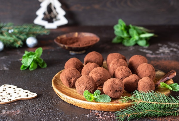 Donkere chocoladetruffels met rauw cacaopoeder, munt en dennentakken. kerst samenstelling.