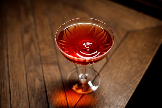 Donkere coctail aan de houten bar die close-up plaatst