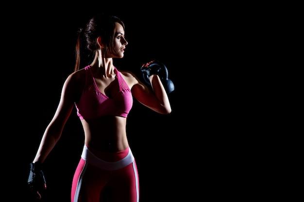 Donkere contrastfoto van jonge mooie geschiktheidsvrouw die die in gymnastiek opleiden.