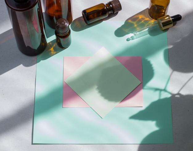 Donkere cosmetische flessen en groene natuurlijke bladeren