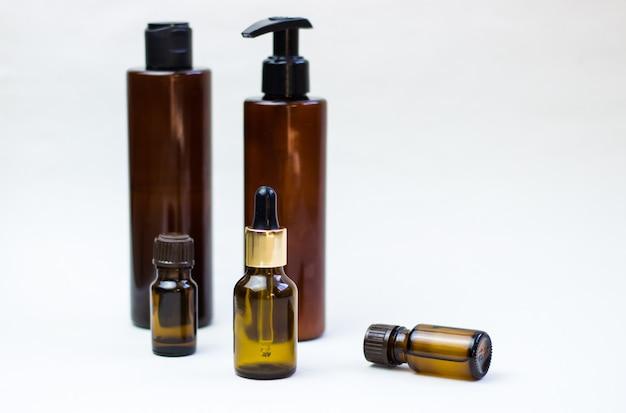 Donkere cosmetische flessen op een lichte achtergrond