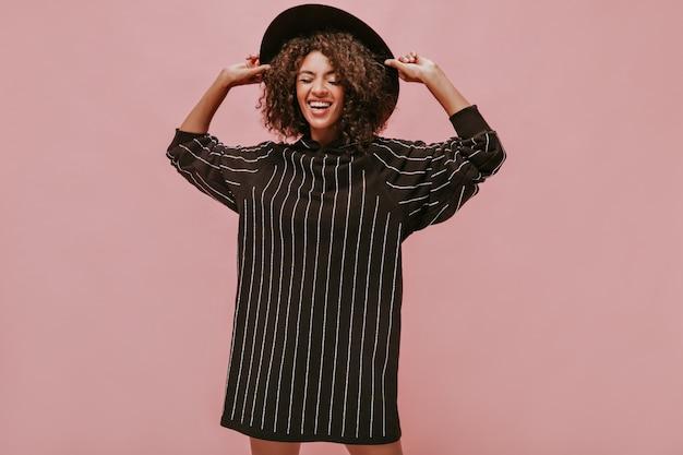 Donkere dame met golvend haar in gestreepte zwarte kleding glimlachend met gesloten ogen en met moderne donkere hoed op geïsoleerde muur..