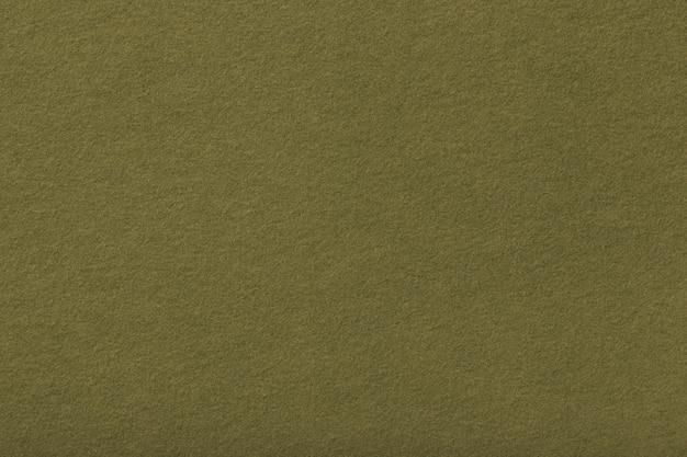 Donkere de stoffenclose-up van het olijf matte suède. fluwelen textuur van vilt.
