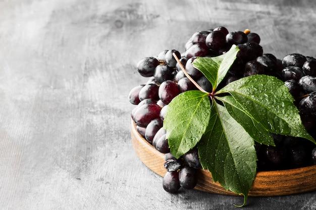 Donkere druiven in houten kom