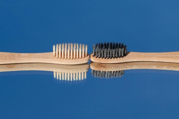 Donkere en lichte bamboetandenborstels worden in de spiegel weerspiegeld tegen de blauwe lucht.