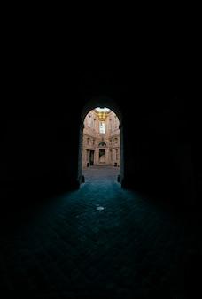 Donkere gang met gewelfde deuropening met uitzicht op een betonnen gebouw
