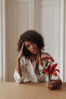 Donkere, gekrulde serieuze vrouw leunt op tafel, raakt het gezicht aan, kijkt naar voren en houdt een vaas met rode bloemen vast in een gezellige kamer