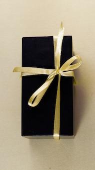 Donkere geschenkdoos met gouden lint in minimalistische stijl geïsoleerd op gouden achtergrond