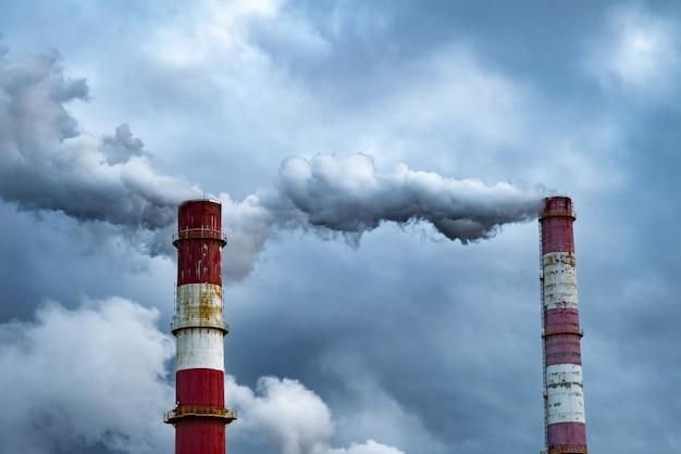Donkere giftige rookwolken die uit fabrieksschoorsteen komen.