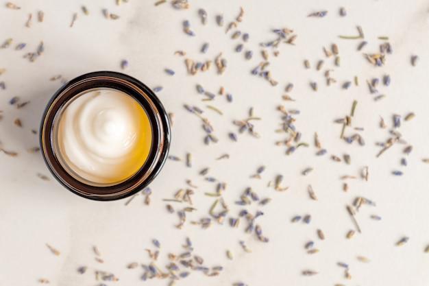 Donkere glazen pot met crème van lavendel, verspreide bloemen van gedroogde paarse lavendel bloesem op marmeren tafel.