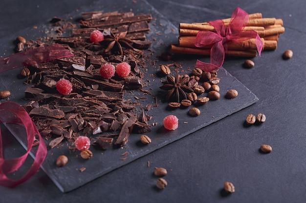Donkere hakkende chocolade, zwart gebrande koffiebonen, rode bessen met kruiden, kaneel en anijs op leisteen bord over zwarte textuurachtergrond. chocoladedessert, zoetwaren en snoepconcept