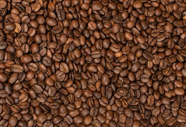 Donkere hele koffiebonen op bruine achtergrond met copyspace.