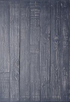 Donkere houten achtergrond gemaakt van een smal bord, geverfd in donkergrijs.