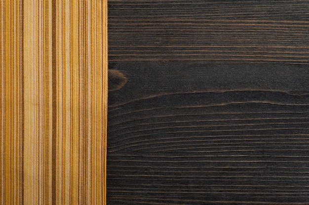 Donkere houten achtergrond met gele servet