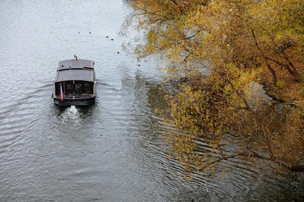 Donkere houten boot die met de stroom van rivier gaat