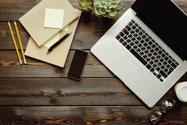 Donkere houten tafel met laptop, kladblok bovenaanzicht