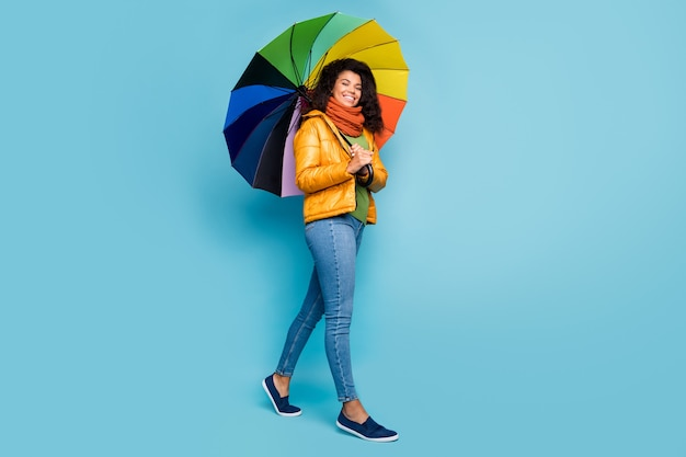 Donkere huid dame lopen met regenboog kleur paraplu op blauwe achtergrond