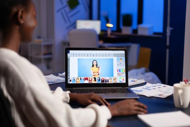 Donkere huid freelancer retoucher vrouw overuren op laptop met fotobewerkingssoftware