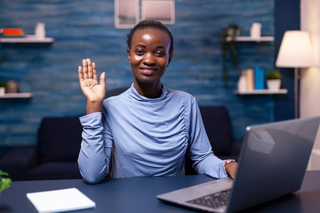 Donkere huid freelancer vrouw zwaaien naar camera in de loop van videoconferentie zwarte freelancer werkt met team op afstand chatten virtuele online conferentie.