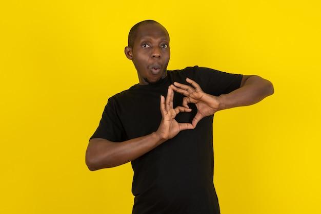 Donkere jonge man die hartgebaar geeft op gele muur
