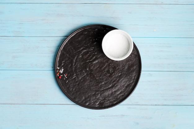 Donkere keramische plaat met kruiden en kom zout op een lichtblauwe houten achtergrond.