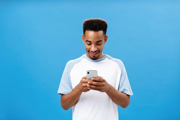 Donkere kerel sms't met geweldig meisje via dating-app met smartphone die op het scherm van de mobiele telefoon kijkt met een geamuseerde geamuseerde uitdrukking die een coole app speelt terwijl hij over een blauwe achtergrond staat