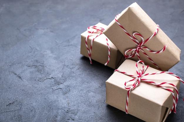 Donkere kerst. bruin pakket van kraftpapier dat met rood en wit koord op zwart wordt gebonden