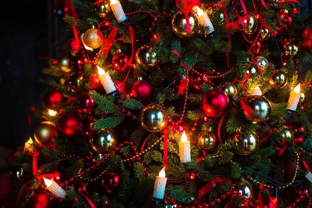 Donkere kerstboom sneeuw bedekt met speelgoed en knipperende kaarsenslinger