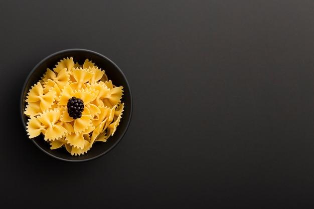 Donkere kom met pasta op een donkere achtergrond