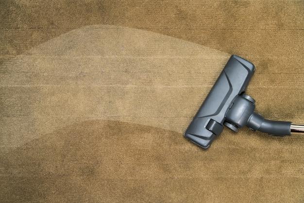 Donkere kop van een moderne stofzuiger die wordt gebruikt tijdens het stofzuigen van een kleed.