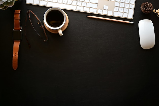 Donkere lederen bureau tafel met desktopcomputer, notitieblok openen, koffiemok