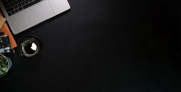 Donkere lederen bureau tafel met laptop en benodigdheden. bovenaanzicht met kopie ruimte