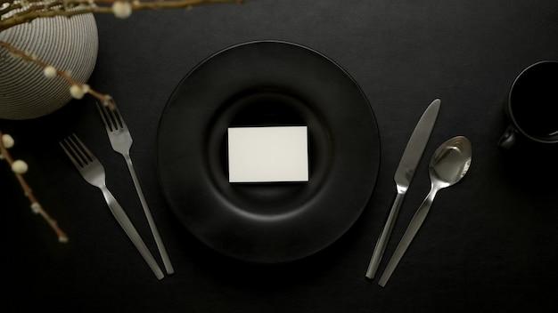 Donkere luxe eettafel setting met plaats cacd op zwarte keramische plaat, zilverwerk en decoratie