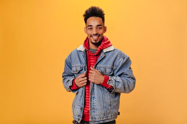Donkere man in stijlvolle outfit met een glimlach die zich voordeed op oranje muur