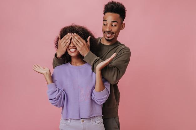 Donkere man sluit de ogen van zijn vriendin op roze muur. donkerbruine vrouw kijkt verbaasd