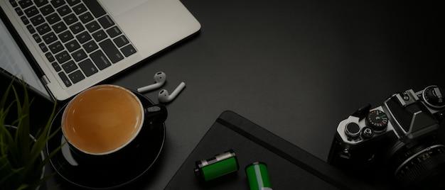 Donkere moderne fotograaf werkruimte met kopie ruimte, laptop, camera, koffiekopje en benodigdheden