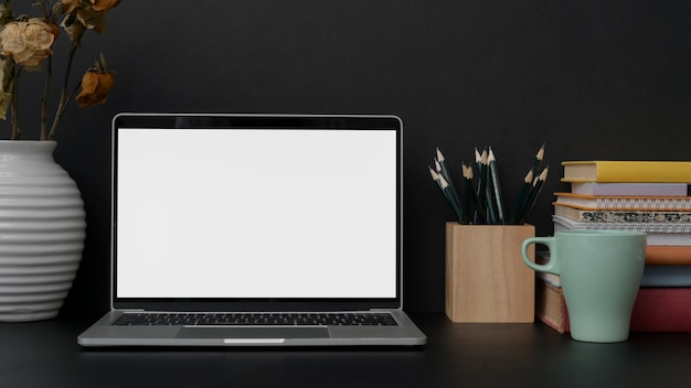 Donkere moderne werkplek met leeg scherm laptop, briefpapier en decoraties