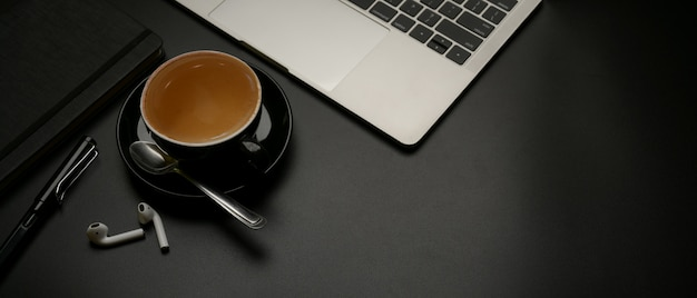 Donkere moderne werktafel met koffiekopje, laptop, briefpapier, draadloze oortelefoon en kopie ruimte